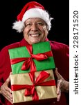 Small photo of Male Senior brimming over with mirth, while handing over two foot-long presents, wrapped golden and green. Both with bowknot. Red Santa Claus cap and winter coat. Cut out on black. Gift giving theme.