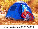 Happy woman enjoying time spending in camp, sitting in the tent in autumn park, active youth, travel and tourism concept - stock photo