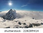 Small photo of Alpinist climbing on Rysy mountain peak over clouds in High Tatras with clear blue sky and on background