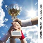 gold cup in hands .   Shutterstock . vector #228339208