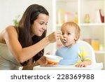 mom spoon feeds baby child boy... | Shutterstock . vector #228369988
