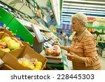 elderly woman weighing goods on ... | Shutterstock . vector #228445303