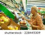 elderly woman weighing goods on ... | Shutterstock . vector #228445309