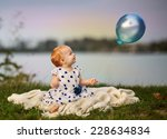 Portrait of a small baby girl at a Lake with blue balloon - stock photo