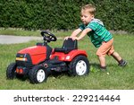 Little Boy Pushing Toy Tractor...