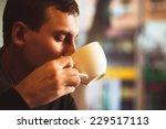 young man drinks coffee on the... | Shutterstock . vector #229517113