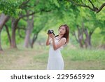 young lady with camera outside | Shutterstock . vector #229565929