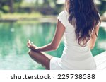 Stock photo close up rear view of slim woman meditating in a lotus yoga position at the poolside 229738588