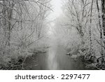 A forest and river photographed during a snow storm. - stock photo