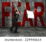 Small photo of businessman holding sledgehammer hitting red FEAR word on concrete wall with large blank hole, overcoming fear concept.