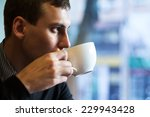 young man drinking coffee in... | Shutterstock . vector #229943428