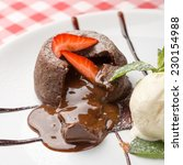 Small photo of Chocolate fondant lava cake decorated with strawberries and vanilla ice cream on the table. Close up