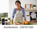 smiling woman preparing salad... | Shutterstock . vector #230767183