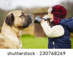 Stock photo little boy with camera is shooting his dog 230768269
