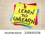Small photo of learn to unlearn - advice or motivation words on a sticky note against burlap canvas