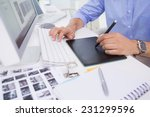 Stock photo graphic designer using digitizer at his desk in creative office 231299596
