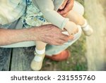 baby girl holding finger of... | Shutterstock . vector #231555760