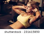 focused beautiful athletic woman working ab intervals - professional fitness and bodybuilding competitor workout in health club gym exercise abs