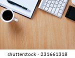 Small photo of Close up Wooden Table of Businessman with Notebook and Pen, Computer Keyboard, Mobile Phone and A Cup of Black Coffee to Stay as Stress Reliever.