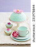 Small photo of Round cake and cupcakes decorated with fondant and gum paste flowers