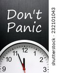 Small photo of The phrase Don't Panic written on a blackboard above a clock with the time set at five minutes to or almost midnight or high noon