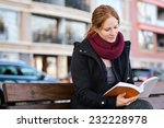 a young woman reads a book on a ... | Shutterstock . vector #232228978