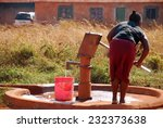 A Woman And Pump Water From A...
