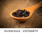 black pepper on wooden spoon and wood background - stock photo
