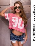 Small photo of Yes sir! Beautiful young woman in sunglasses holding hand near head and looking at camera while standing against metal background