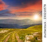 road among white sharp stones on the hillside on top of mountain range at sunset - stock photo