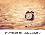 Small photo of Vacation time concept alarm clock on beach of lipe island, thailand. Retro filter