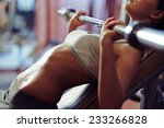 woman lifting weights in gym | Shutterstock . vector #233266828