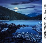 view on lake with rocky shore and some boulders near pine forest on mountain  with high vista far away at night in full moon light - stock photo