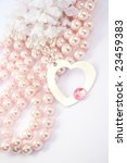 Necklace with heart medallion with pink stone on it, pink pearls and white fabric flowers.. - stock photo