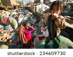 Small photo of KATHMANDU, NEPAL - DEC 24, 2013: Unidentified child and his parents during lunch in break between working on dump. Only 35% of population Nepal have access to adequate sanitation.