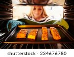 Woman Putting Salmon Fillets...