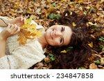 brunette woman lying on autumn... | Shutterstock . vector #234847858