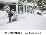 Man Using Snowblower To Clear...