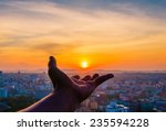 Stock photo hand holding sunset and city of background 235594228
