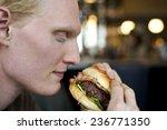 young man eating big burger   Shutterstock . vector #236771350