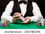 Small photo of casino, gambling, poker, people and entertainment concept - close up of holdem dealer shuffling playing cards deck and chips on green table