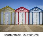 three colourfull beach huts on...