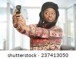 Black woman taking a selfie inside an office building - stock photo