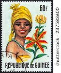"Small photo of GUINEA - CIRCA 1966: A stamp printed in Guinea from the ""Guinean Flora and Female Headdresses "" issue shows Ammocharis and Woman, circa 1966."