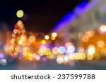 abstract blur of christmas tree on old european city street at night - stock photo