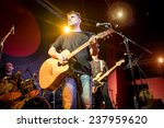 Band performs on stage, rock music concert in a nightclub. Warning - authentic shooting with high iso in challenging lighting conditions. A little bit grain and blurred motion effects. - stock photo