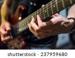 musician plays a guitar closeup. Warning - authentic shooting with high iso in challenging lighting conditions. A little bit grain and blurred motion effects. - stock photo