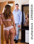 Small photo of Handsome man is tempted by beautiful girl in the underwear on threshold