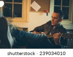 man playing guitar at home... | Shutterstock . vector #239034010