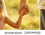 a parent holds the hand of a... | Shutterstock . vector #239299030